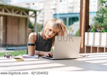 Beautiful Serious Thinking Woman Working At Laptop Outside And Drinking Coffee. Using Computer And O