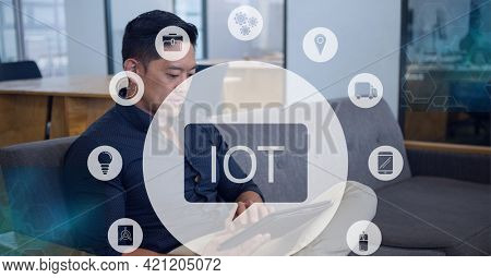 Composition of iot icon with network of connections over man using tablet. global internet of things connections, business, networking and digital interface concept digitally generated image.