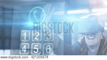 Composition of happy woman wearing vr headset touching digital phone dialing screen. global online business, networking and digital interface concept digitally generated image.