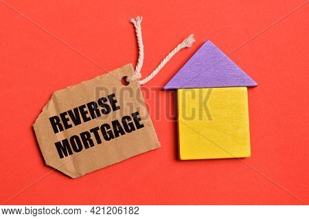 Top View Of Toy House And Label Tag Written With Reverse Mortgage. Real Estate Concept.