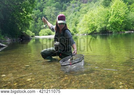 young woman fly fishing and catching a brown trout
