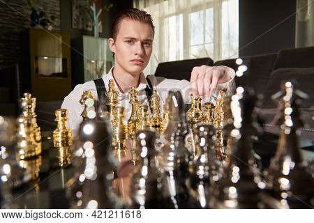 Well-groomed smart man in elegant clothes plays chess in a modern luxury interior. Strategic decision in business.