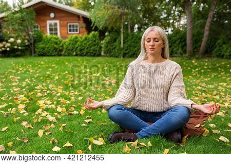 Lawn Is Covered With Yellow Autumn Leaves. Woman Sitting Cross Legged In Lotus Position And Meditati