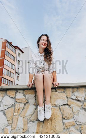 Smiling Girl Sitting On A Stone Wall On A Street Background. Happy Girl With Long Hair And Shorts On