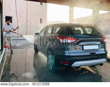 A Man Washes His Car At A Self-service Car Wash In Summer.