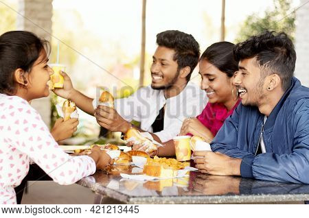 Focus On Front Boy, Group Of Friends Having Fun And Laughing While Together Eating Breakfast At Rest