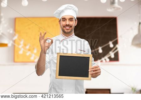 cooking, culinary and people concept - happy smiling male chef in toque showing chalkboard and ok hand sign over restaurant background