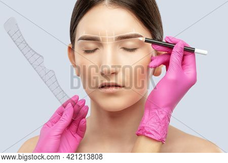 Make-up Artist Makes Markings With White Pencil For Eyebrow And Paints Eyebrows. Professional Makeup