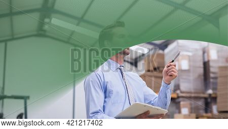 Green technology background over caucasian supervisor checking stock in warehouse. global logistics business and technology concept