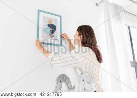 home improvement, decoration and people concept - happy smiling woman on ladder decorating home with art