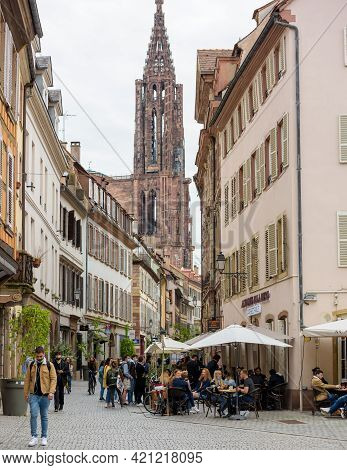 Strasbourg, France - May 19, 2021: Notre-dame Cathedral And People Drinking At The Terrace Of Academ