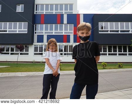 A Blond Boy 8 Years Old And A Blond Girl 7 Years Old Are Standing Against The Background Of A Modern