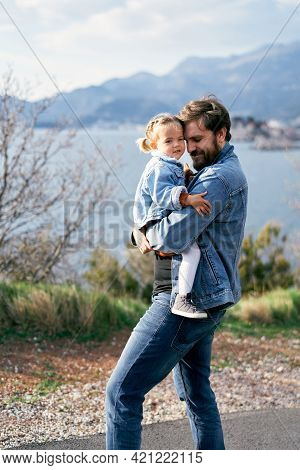 Dad Carries A Little Girl In His Arms, Walking Along The Road Against The Backdrop Of The Sea, Mount