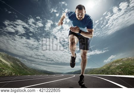 Professional Male Runner, Jogger On Road And Sky Background. Caucasian Fit Athlete Practicing, Train