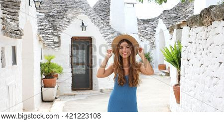Beautiful Young Woman With Blue Dress And Hat Walking In Old Town Street Of Alberobello, Panoramic B