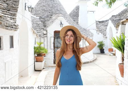 Curious Young Woman With Blue Dress And Hat Walking In Old Town Street Of Alberobello, Apulia, Italy