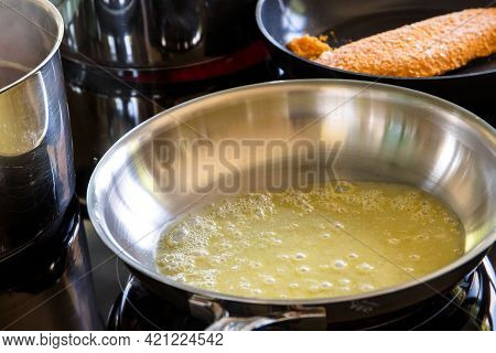 An Induction Cooker With Some Stainless Steel Pans And Pots On Them. One Of The Pans Has Molten Fizz