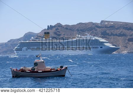 A Cruise Ship And A Fishing Boat Sailing In The Caldera Of The Island Of Santorini In Greece. In The