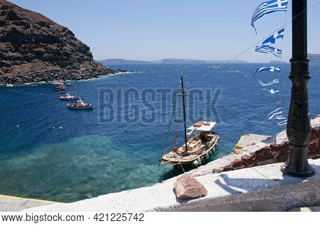 Fishing Boats On The Clear Turquoise Waters Of The Aegean Sea At The Old Amoudi Harbor Of The Villag