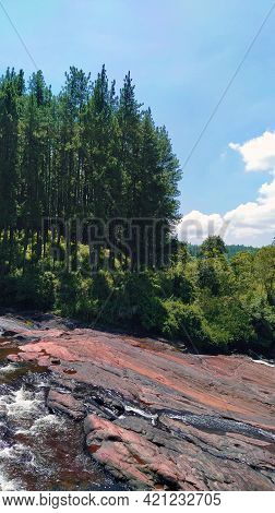 Beautiful Scenery Of A Pine Forest Over A Scenic Stone Plain Where An Attractive Waterfall Begins -