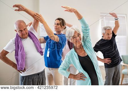 Active seniors doing exercise with physiotherapist at nursing home gym. Trainer helping elderly man and old woman exercising at home. Retired people doing stretching exercises at retirement community.