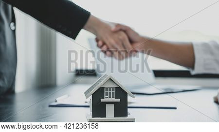 Home Model. Real Estate Agents And Buyers Handshake After Signing A Business Contract, Renting, Buyi