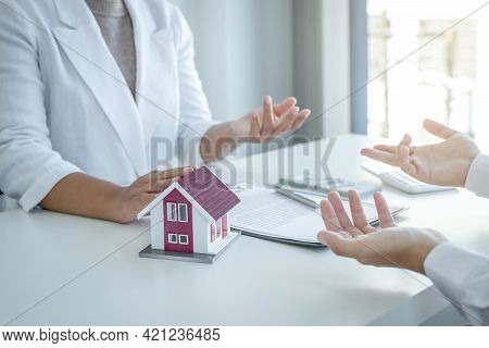 Home Model. The Real Estate Agent Explains The Business Contract, Rent, Purchase, Mortgage, A Loan,