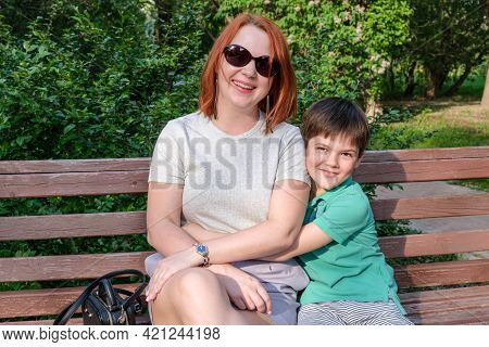 Young Woman With Red Hair And Boy Are Sitting In Park On Bench And Smile. Son Hugs His Mother Gently