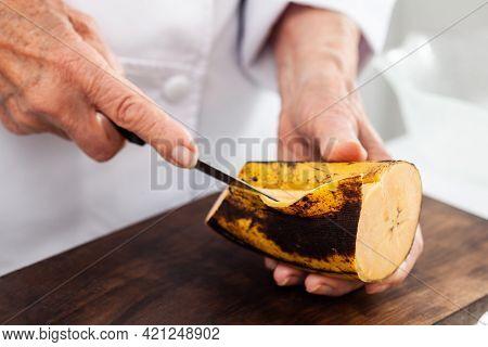 Closeup Of A Senior Woman Hands While Peeling A Ripe Plantain