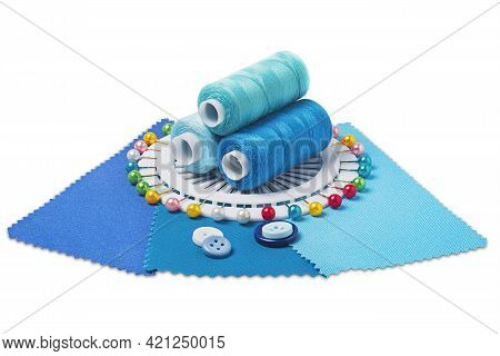 Sewing  Thread, Needle, Bobbins, Buttons And Fabric Samples In Blue, Light Blue Color On Isolated Wh