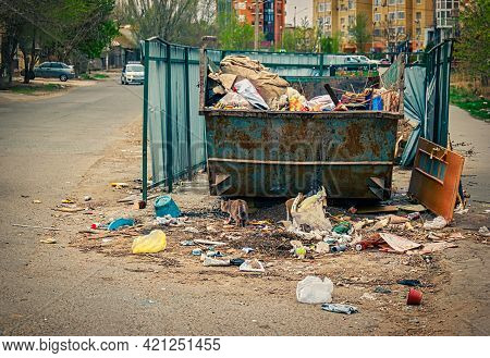 Overfilled Trash Dumpster In Ghetto Neigborhood. A Lot Of Litter About