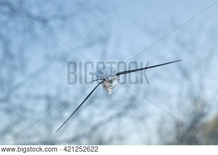 Broken Window Glass With A Bullet Hole, Damaged Glass With Traces Stone Or From Bullet Trace In Glas