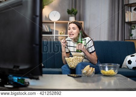 Excited Caucasian Woman Sitting With Beer And Snacks On Couch And Cheering Favorite Team During Foot