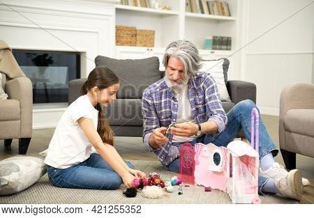 Loving Grandfather And Adorable Little Girl Granddaughter Playing With Toys While Sitting On Living