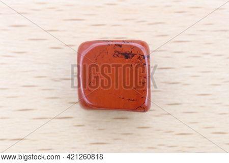 Red Jasper Jewel Stone Texture On Light Varnished Wood Background. Macro Closeup.
