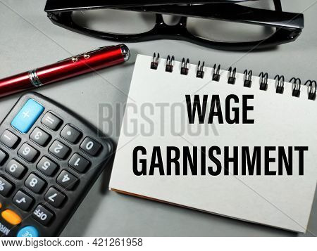 Business Concept.text Wage Garnishment With Notebook,pen,glasses And Calculator On Gray Background.