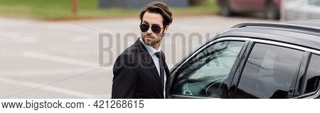 Bearded Bodyguard In Suit And Sunglasses With Security Earpiece Near Modern Auto, Banner.