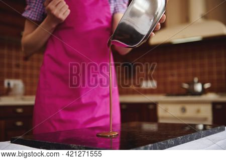 Professional Confectioner Chocolatier In Pink Apron Pouring Chocolate Mass From Bowl Into Marble Sur