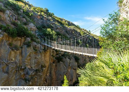 A Young Girl Crossing The Wooden Suspension Bridges. Ruta De Los Pantaneros In The Town Of Chulilla
