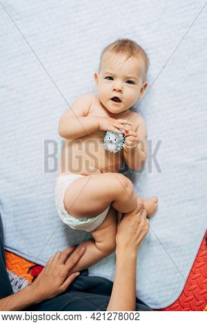 Mom Holds Baby In A Diaper With A Toy Hedgehog In His Hands By The Legs. Baby Lies On A Bedspread On