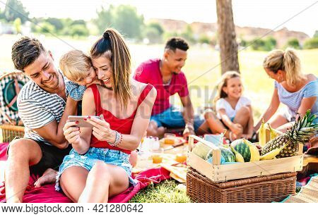Happy Multiethnic Families Playing With Phone At Pic Nic Garden Party - Joy And Love Life Style Conc