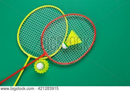 Two Shuttlecock And Badminton Racket. On A Green Background. Concept Summer Relaxation.