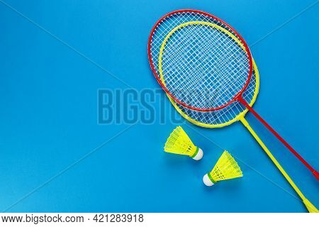 Two Shuttlecock And Badminton Rackets On Blue Background. Active Recreation And Sports Concept. Spac