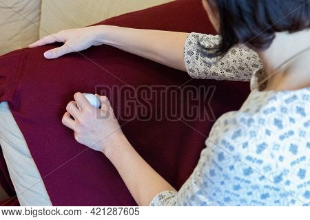A Woman Removes Wool Pellets On Clothes With A Device While Sitting On A Sofa In An Apartment.