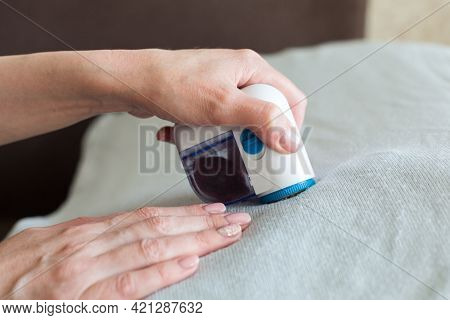 Removal Of Wool Pellets By The Device On Everyday Clothes Close-up.