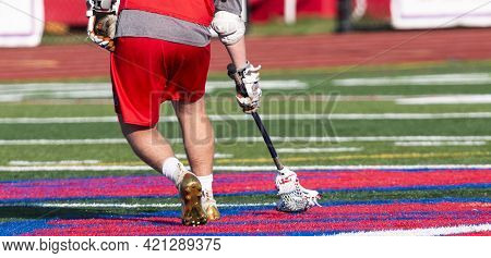 Rear View Of A High School Lacrosse Player Scooping Up The Ball While Runneing Down The Field During