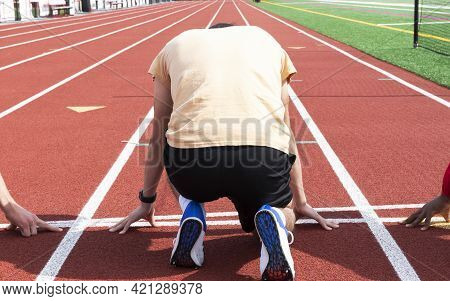 Rear View Of A High School Track Runner Is At The Starting Line On His Mark Ready To Sprint Down The