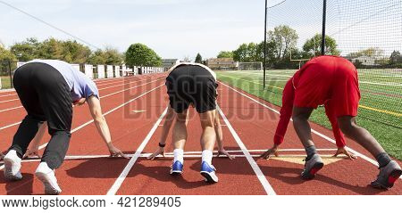 Rear View Of Three High School Track Sprinters In The Set Position At The Starting Line Ready To Run
