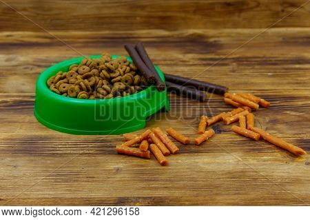 Dog Delicacy Food And Feed In Green Plastic Bowl On Wooden Background. Dog Care Concept