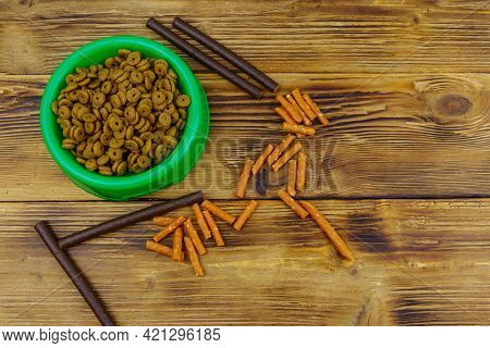 Dog Delicacy Food And Feed In Green Plastic Bowl On Wooden Background. Top View. Dog Care Concept